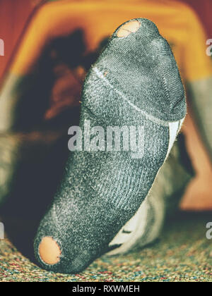 Close up of a young boys feet with holes in his socks - Stock Photo