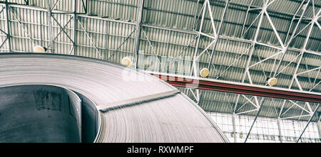 Industrial warehouse with rolls of steel sheet in a plant galvanized steel coil. Coil on foreground, ceiling on background - Stock Photo