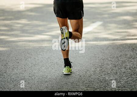 back legs male runner running on gray asphalt - Stock Photo