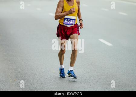 elderly male athlete runner running on gray asphalt road - Stock Photo