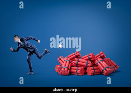 Businessman running away from pack of red tnt dynamite sticks with lighted fuse on blue background - Stock Photo