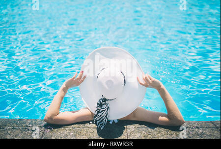 Young woman happy in big hat relaxing on the swimming pool, travel near the beach in the sunset. Concept summer - Stock Photo