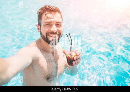 Happy bearded man making selfie in swimming pool. He is drinking a cocktail and relaxing. - Stock Photo