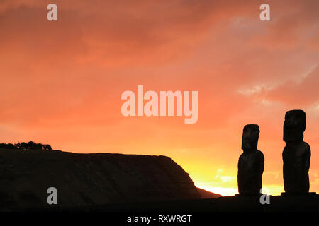 Silhouette of two of 15 huge Moai statues at Ahu Tongariki against orange color sunrise sky, Archaeological site in Easter Island, Chile - Stock Photo