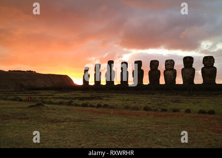 Silhouette of nine of 15 huge Moai statues at Ahu Tongariki against orange color sunrise sky, Archaeological site in Easter Island, Chile - Stock Photo