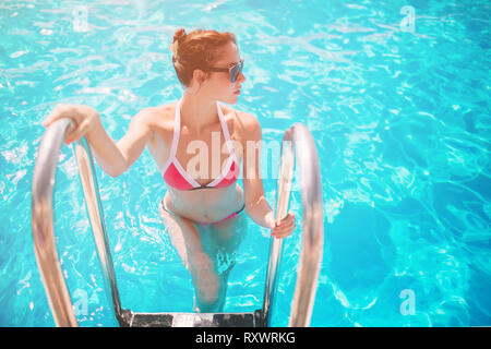 Summer photo of woman in swimming pool. Happy female model in water on summer vacations - Stock Photo
