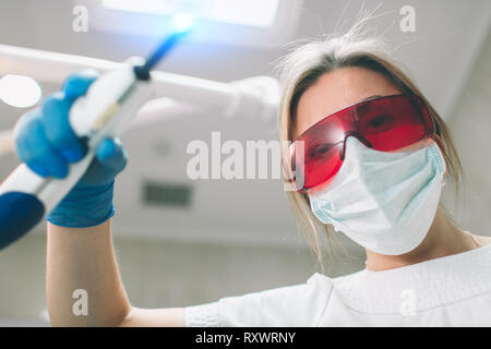 Portrait of female dentist . She examining a patient's teeth . - Stock Photo