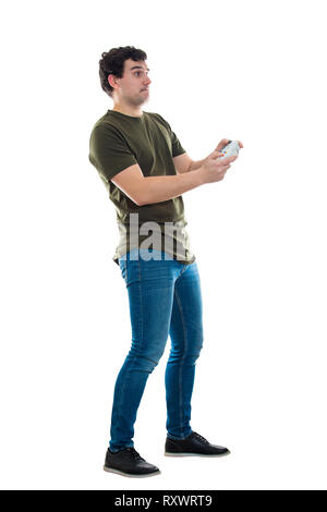 Addicted young man playing video games isolated over white background. Excited guy stand all ears holding a joystick console looking attentive try to  - Stock Photo