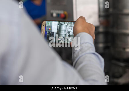 A man taking video with mobile phone the process of filling steel beer barrels with fresh beer in brewery plant factory - Stock Photo