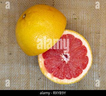 Fresh juicy pink grapefruit halves on a hessian background - Stock Photo