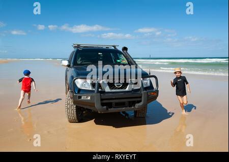 children running around a parked car on a beach - Stock Photo