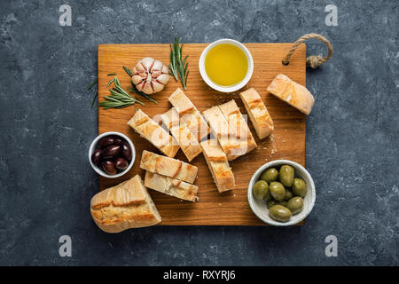 Italian food concept. Cooking Italian bruschetta. Olives, fresh baguette slices, olive oil, garlic and rosemary on dark stone background top view