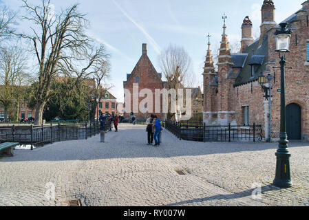 BRUGES, BELGIUM - FEBRUARY 17, 2019: walk through city sights, tourist route. Medieval buildings and water channels - Stock Photo