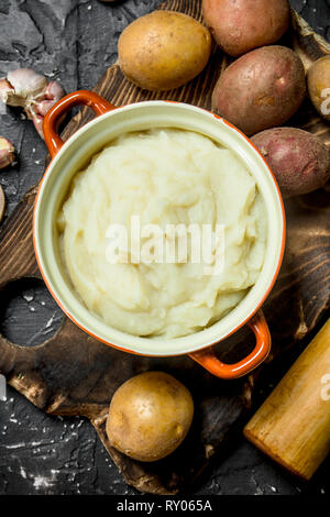 Mashed potatoes in a bowl with garlic . On black rustic background. - Stock Photo