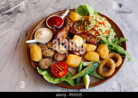 Delicious restaurahnt appetizers set for beer. Delicious restaurant appetizers set for beer. vegetable salad, boiled potatoes, grilled chicken legs - Stock Photo
