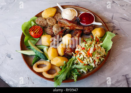 Delicious restaurahnt appetizers set for beer.ketchup and mayo laying on clay plate. - Stock Photo