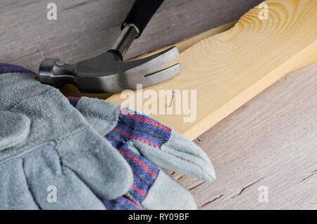 Work on the construction or repair of the house. Independent update, renovation. Use working gloves and a hammer. Concept for DIY, workplace safety, w - Stock Photo