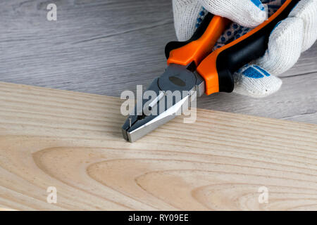 Work on the construction or repair of the house. Independent update, renovation. Use of working gloves and pliers. Concept for DIY, workplace safety,  - Stock Photo