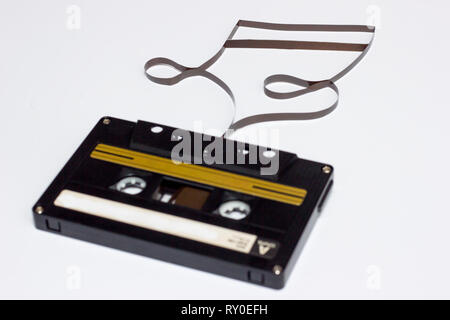 Music note sign. Cassette tape on white background. Film shaping music note. - Stock Photo