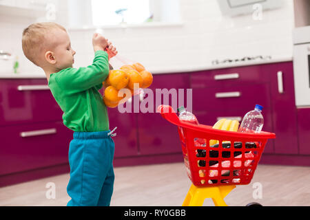 Little boy holds a grid with oranges. Little kid in casual wear carrying child plastic shopping trolley. - Stock Photo