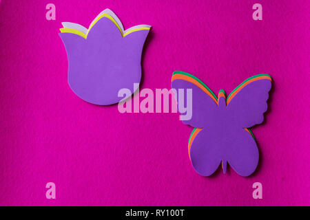 Violet butterfly and flower made of soft material on fuchsia background - Stock Photo