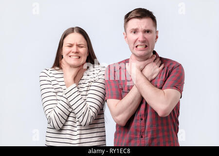 throat pain. Two sick young woman and man standing holding neck because feeling pain. - Stock Photo