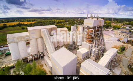 Aerial view of the factory of limestones. Seen the white buildings stones and machineries working inside the area - Stock Photo