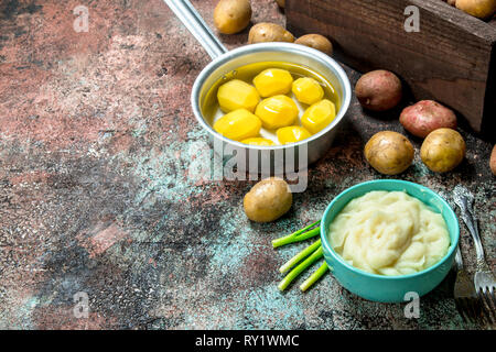 Mashed potatoes in a bowl with green onions . On a rustic background. - Stock Photo