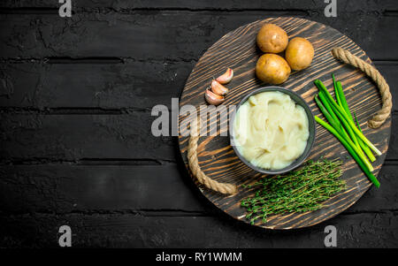 Mashed potatoes in a bowl with herbs and garlic. On a rustic background. - Stock Photo