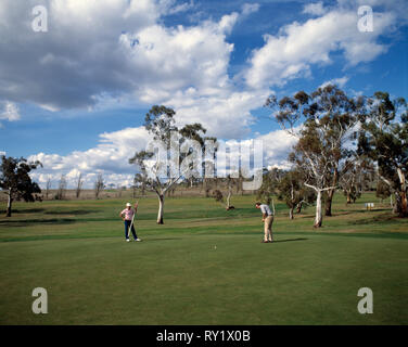 Australia. New South Wales. Snowy Mountains. Cooma golf course. Two men on putting green. - Stock Photo