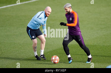 Manchester City's Sergio Aguero attempts to dribble the ball past a Manchester City staff member during the training session at the City Football Academy, Manchester. - Stock Photo