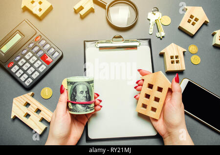 A girl holds in his hands a dollars and a miniature house. The concept of risk assessment for the purchase of real estate. Attracting investment in pr - Stock Photo