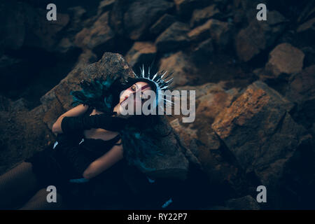 A young woman in the image of a fairy and a sorceress lying on rock in a black dress and a crown. - Stock Photo