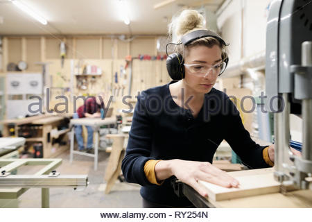 Focused female carpenter using saw in workshop - Stock Photo