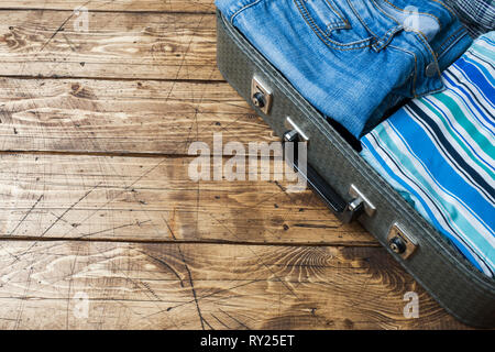 Travel preparations concept with suitcase, clothes and accessories on an old wooden table. Top view Copy space, - Stock Photo