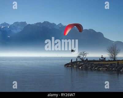 Paraglider tandem landing on little peninsula in lake with alpine mountains in the background. - Stock Photo