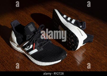 Black Adidas Ultraboost running shoes on hardwood floor - Stock Photo