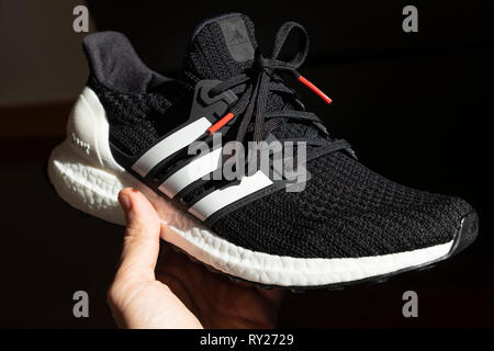 Person holding a black Adidas Ultraboost running shoe - Stock Photo
