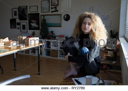 Portrait confident beautiful young woman with long curly blonde hair - Stock Photo