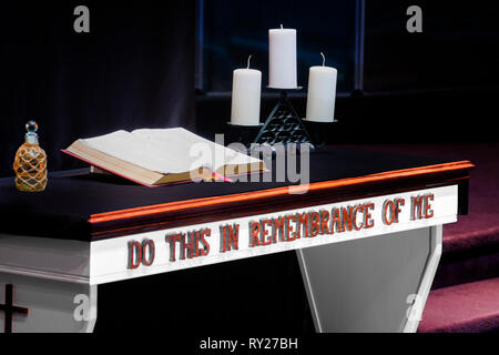 Horizontal shot of a church's Communion Table With a Bible and Candles on it in a Christian Church. - Stock Photo