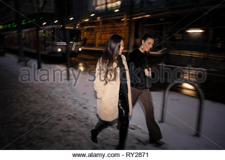 Women friends walking along snowy urban street at night - Stock Photo