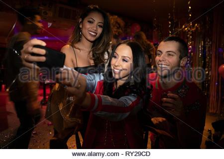 Friends taking selfie in nightclub - Stock Photo