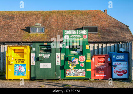 A line of clothing and shoe banks in a supermarket car park. - Stock Photo