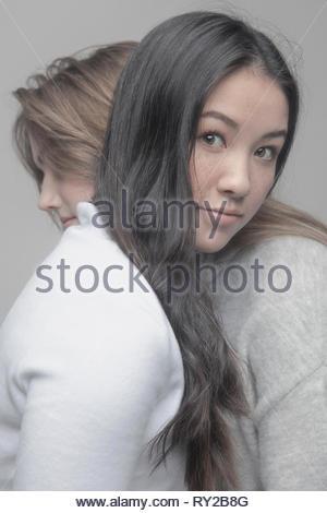 Portrait confident beautiful teenage girl hugging friend - Stock Photo