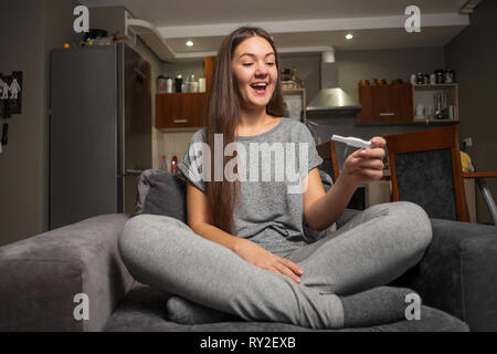 surprised happy young woman and pregnancy test - Stock Photo