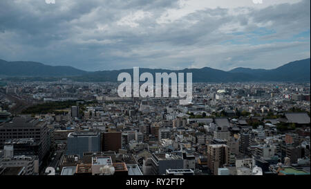 Aerial shots of the city of Kyoto. Skyscrapers and buildings expand out into the distance of the Japanese city as a stormy sky and clouds . - Stock Photo