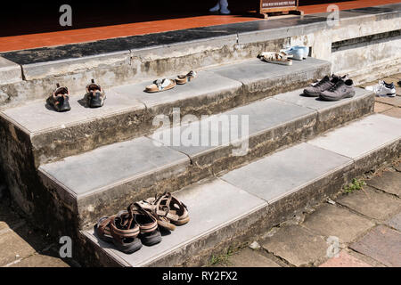 Visitors shoes left on steps outside a temple in Thien Mu Pagoda complex. Hue, Thừa Thien–Hue Province, Vietnam, Asia - Stock Photo