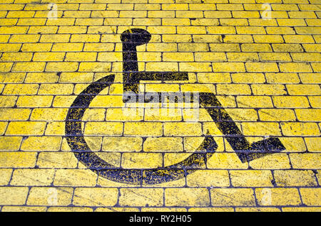 Wheelchair icon in black on yellow pavement indicating a parking place for disabled visitors - Stock Photo