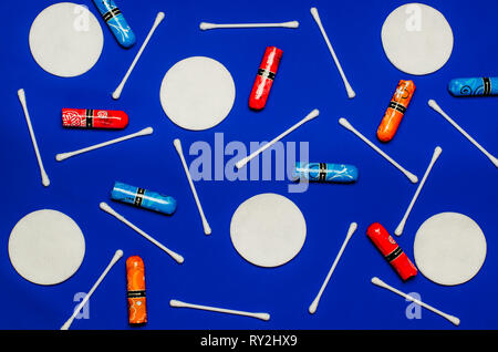 Concept of the menstrual period. Women's Protection of Hygiene. Multicolored flower swabs with colorful petals on a blue background - Stock Photo