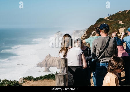Portugal, Sintra, June 26, 2018: A group of people or tourists admire the sights and take pictures of the beautiful view of Cape Roca. - Stock Photo
